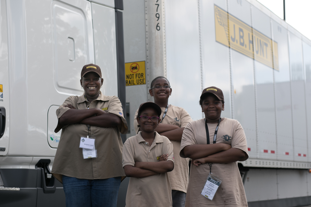 Driver Andrea and her nieces and nephew stand in front of a J.B. Hunt truck with their arms crossed.