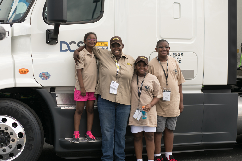 Driver Andrea stands next to her truck with her arms around her nephews and nieces.