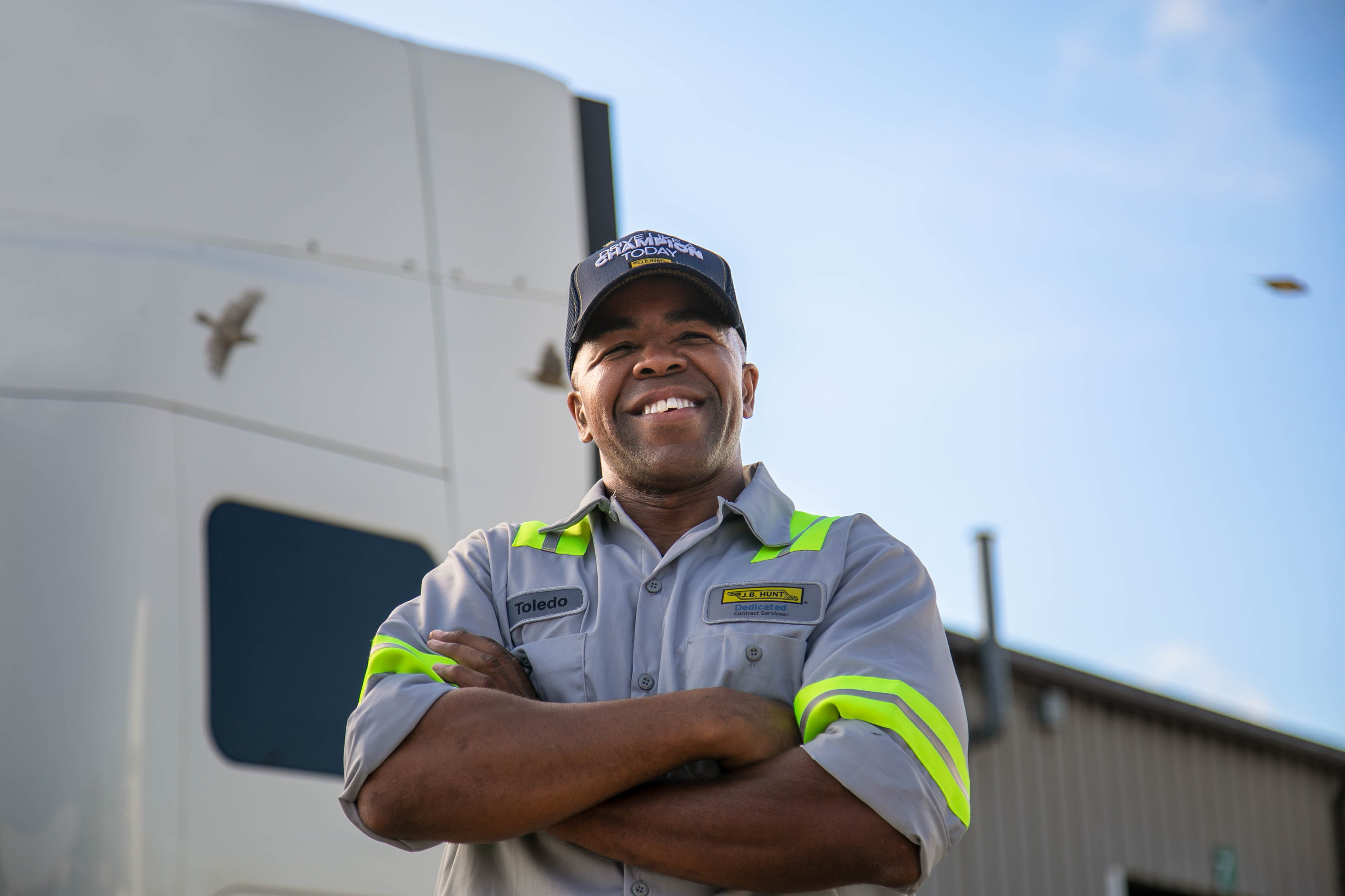 J.B. Hunt driver Toledo smiling with his arms folded in front of a J.B. Hunt sleeper truck.