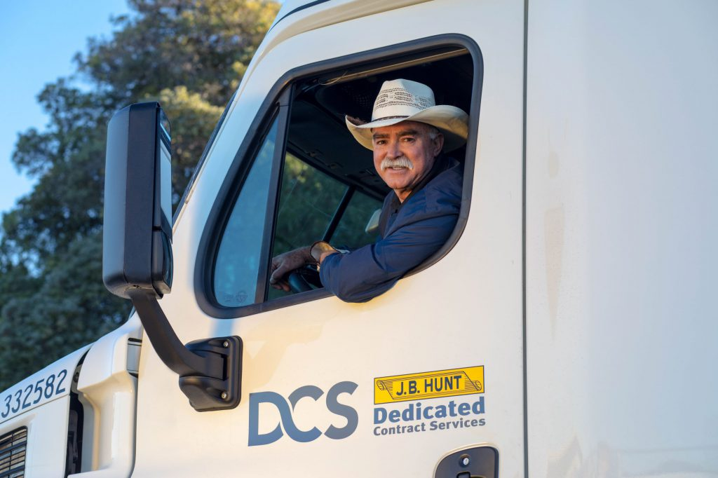 Dedicated driver Juan wearing cowboy hat and smiling while driving tractor-trailer.