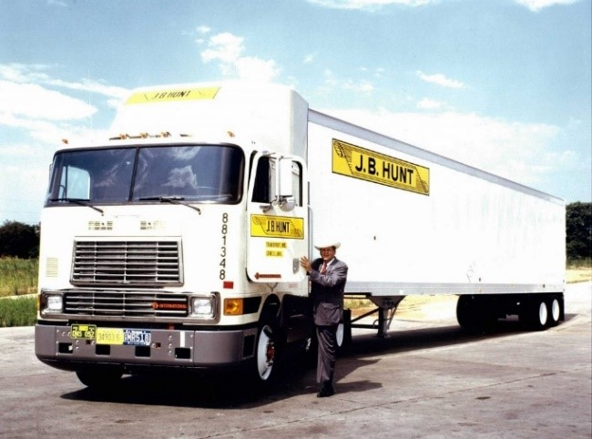 JB Hunt standing next to an early model company tractor-trailer.