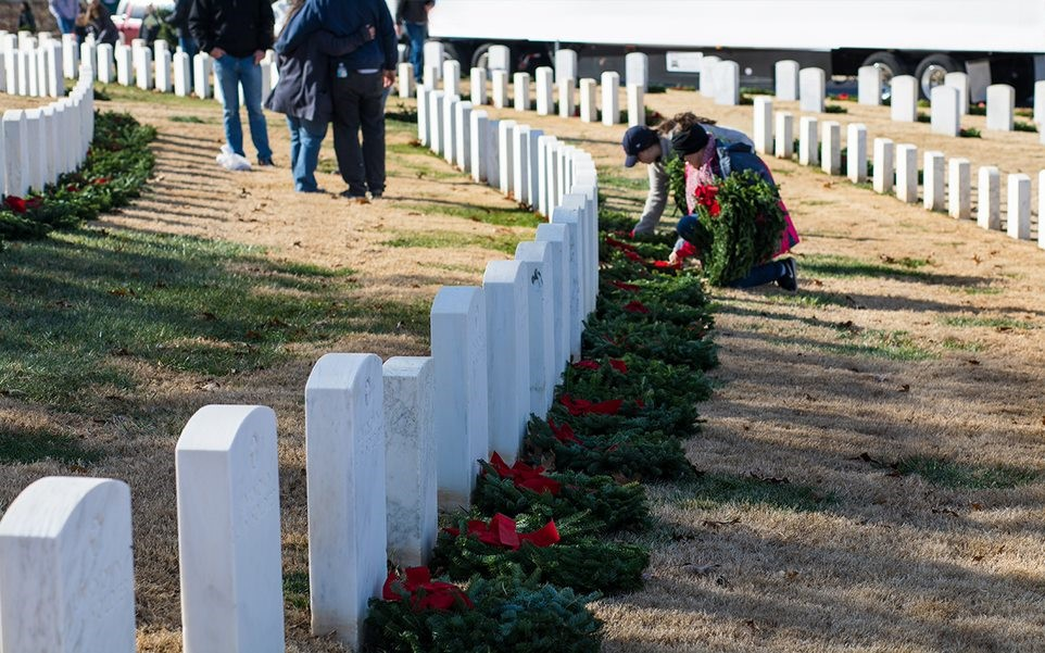 Volunteers lay wreaths at a fallen hero's grave during a Wreaths Across America event.