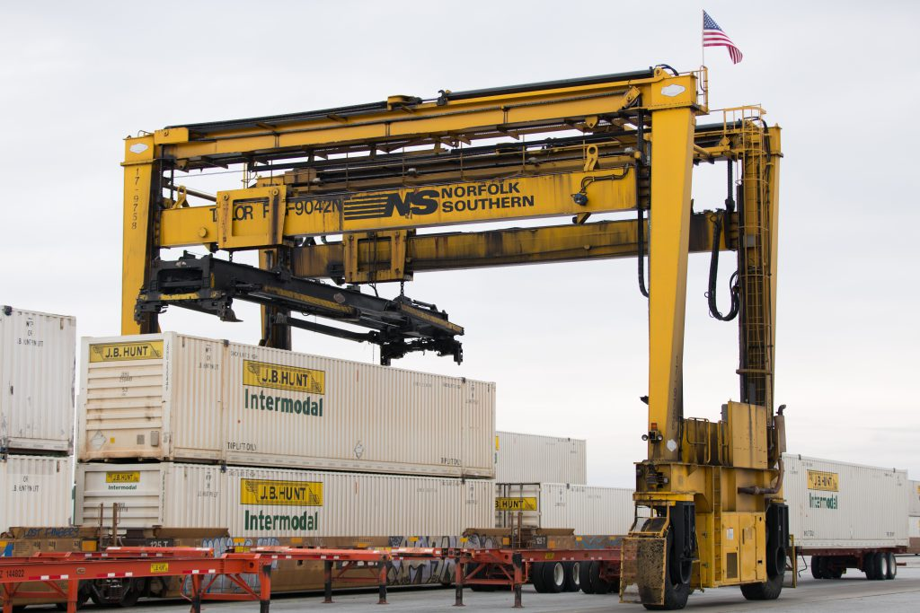 A J.B. Hunt container is lifted off of the rails and onto a chassis at a rail yard.
