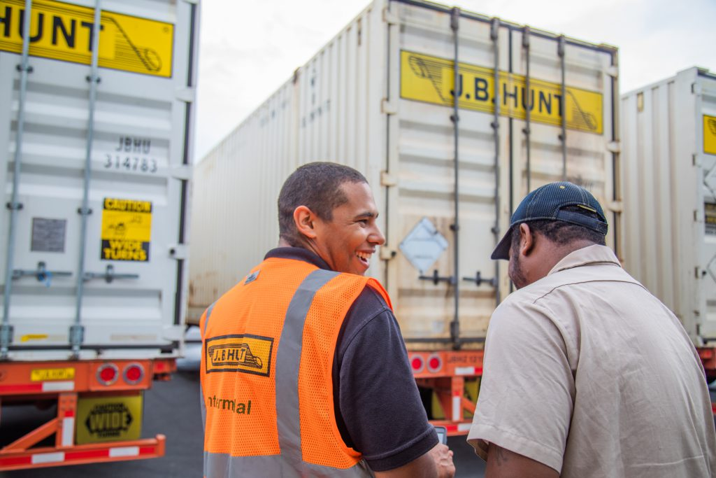 Intermodal driver Robert laughs with fellow driver in front of J.B. Hunt trailers.
