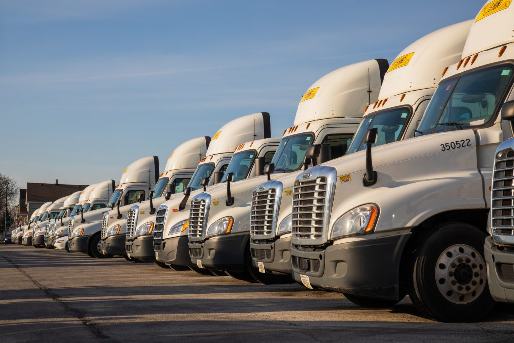 Long line of J.B. Hunt truck cabs in parking lot