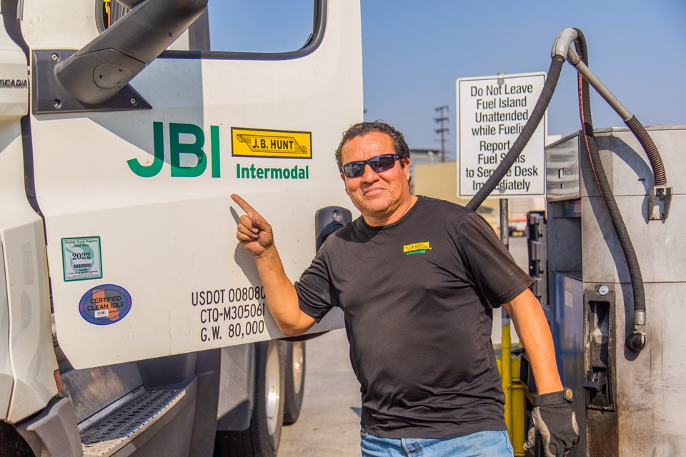 Male J.B. Hunt driver standing in front of day cab, pointing to logo.